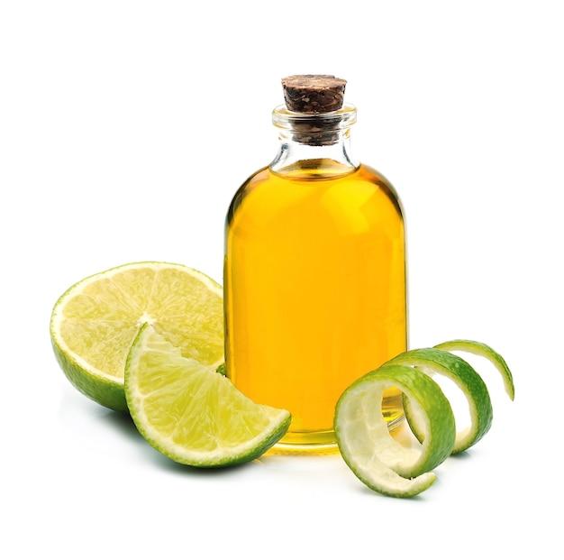 Цитрусовое масло с плодами лайма на белом фоне.