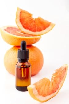 白い背景の上の新鮮なグレープフルーツとガラス瓶の柑橘類またはグレープフルーツのエッセンシャルオイル。スパとスキンケア製品