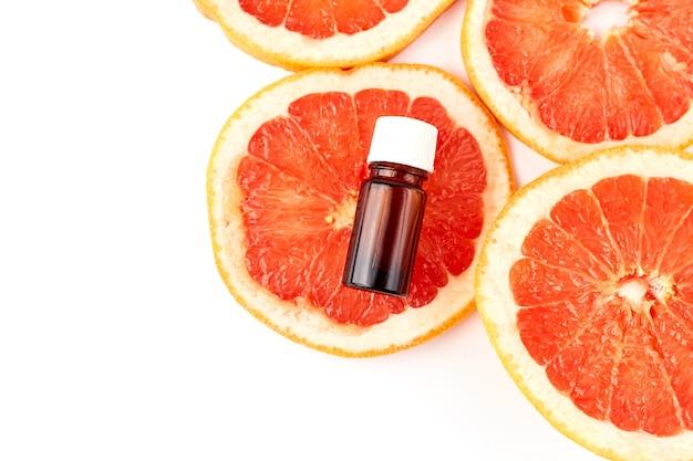 白い表面に新鮮なグレープフルーツとガラス瓶の柑橘類またはグレープフルーツのエッセンシャルオイル