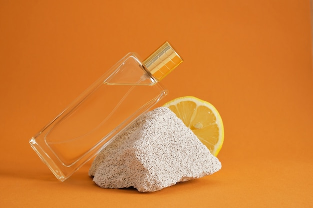 柑橘系の香り、レモンの香りをコンセプトにした香水、コンクリートブロックの破片、レモンスライス、茶色の背景に香水のボトル