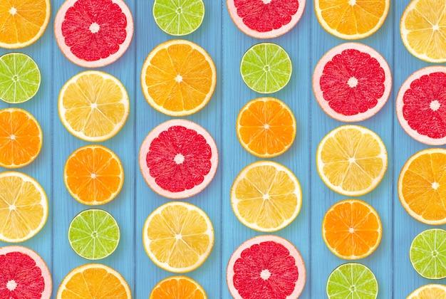 青い木製の背景に柑橘類のスライス