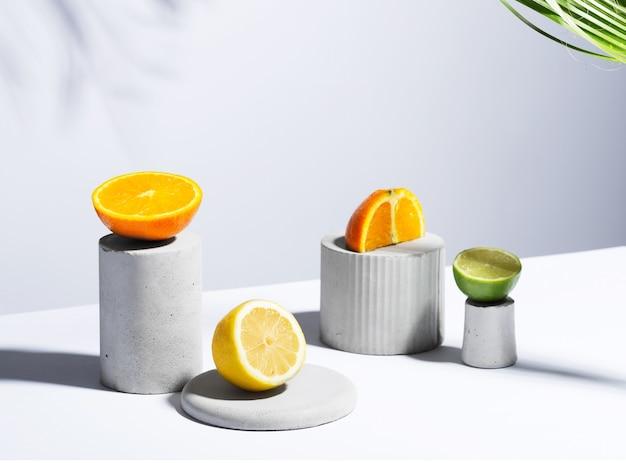 灰色のスタンドと表彰台にレモン、ライム、オレンジの柑橘類の静物コンセプト