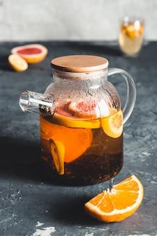 透明なティーポットに入った柑橘系のお茶。灰色の石のテクスチャの背景に。健康ドリンク