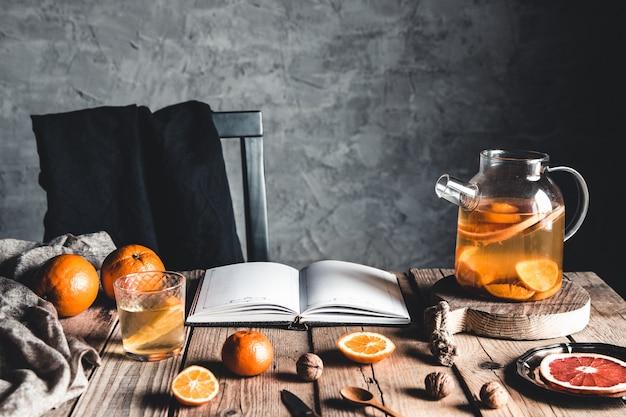 木製のテーブルにグレープフルーツとレモンとテーブルの上の透明なティーポットの柑橘類のお茶。本で、料理。
