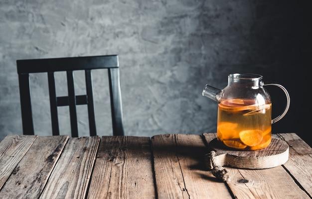 Цитрусовый чай в прозрачном чайнике на столе с грейпфрутом и на деревянном столе. здоровый напиток.