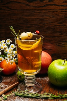 레스토랑의 테이블에 사과와 열매와 투명 머그잔에 감귤류 차 또는 그 로그