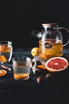 Citrus tea in a transparent teapot on a dark concrete.