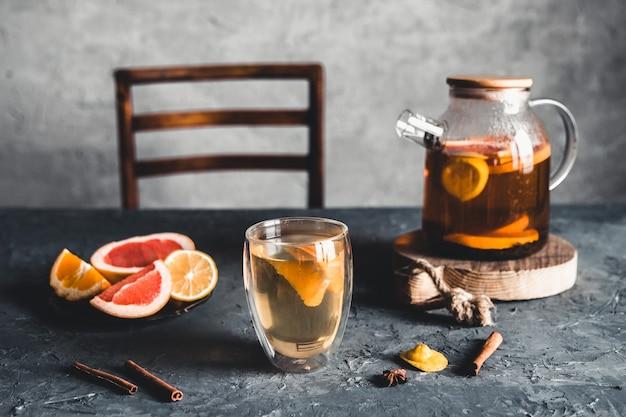 Citrus tea in a transparent teapot on a gray concrete.