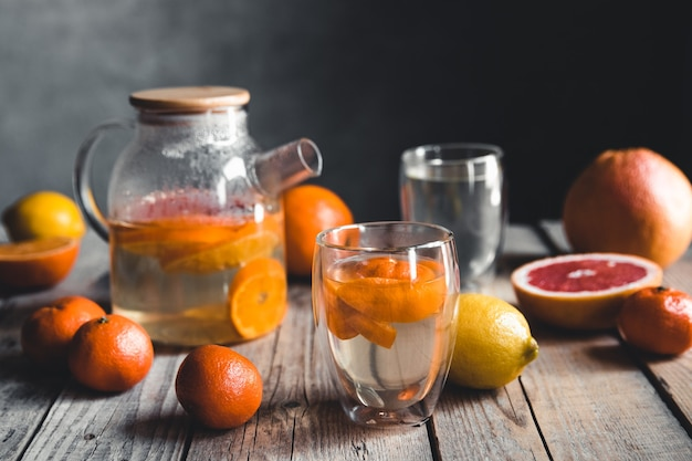 Citrus tea in a transparent teapot on a table with grapefruit and on a wooden table