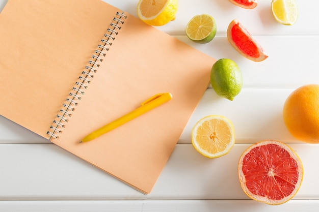 Citrus with notebook on white wooden table
