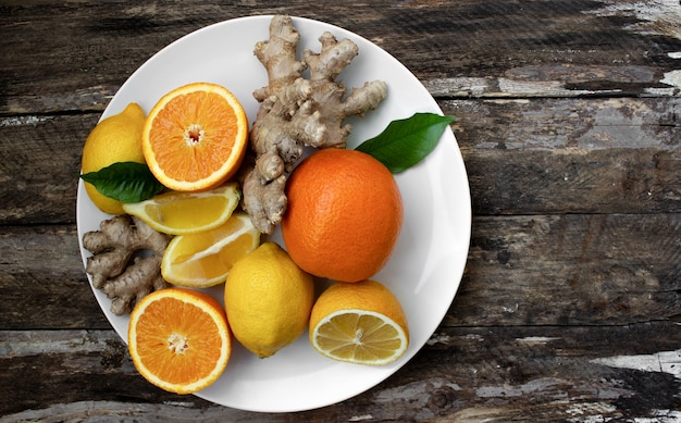 Цитрусы на белой тарелке апельсины лимоны и имбирь на белой тарелке на деревянном фоне