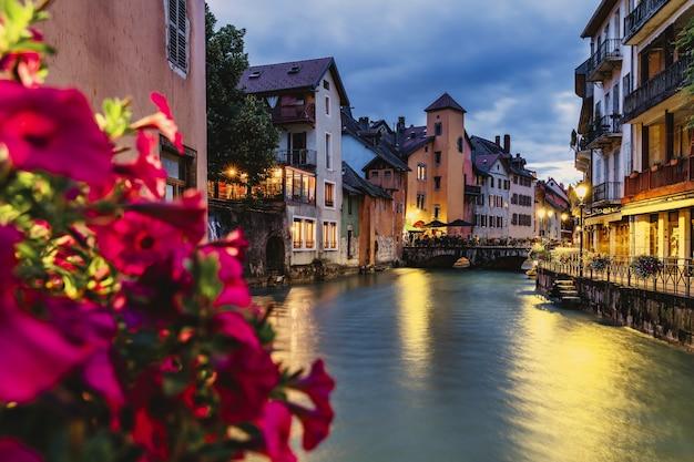 도시 - 전경에 꽃과 함께 강 유역에서 밤에 프랑스 안시의 전망 - 선택적 초점.
