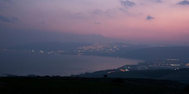 Город на побережье освещался в сумерках, веред ха-галиль, галилейское море, галилея, израиль