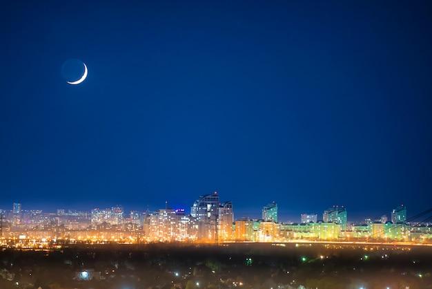 별이 있는 어두운 푸른 하늘에 초승달이 있는 밤의 도시