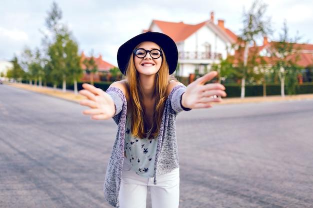 トレンディな白いジーンズ、流行に敏感なメガネ、帽子をかぶって、田舎でポーズをとって、一人で、ソフトフィルムの色を楽しんでいる若い官能的なブロンドの女性の都市秋のファッションライフスタイルの肖像画。