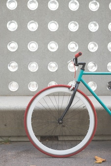 A city bicycle fixed gear on a green and white wall