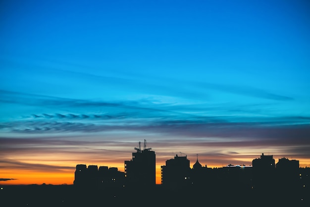 City buildings silhiouettes on background of sunset sky