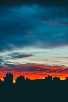 City buildings silhiouettes on vivid background of multicolor sunset sky
