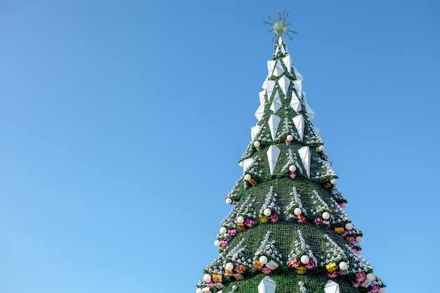 City christmas tree against a blue sky. christmas garlands. weekends and holidays