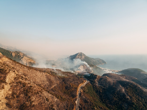 The city on the coast of montenegro is engulfed in fire white smoke over the city the road and the