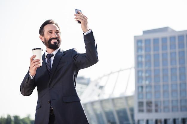 都会の住人。朝のコーヒーを飲みながら彼の街の写真を撮る陽気なひげを生やしたビジネスマン