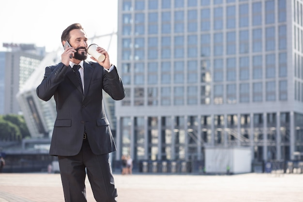 都会の住人。電話で会話しながらコーヒーを飲む陽気なハンサムなビジネスマン