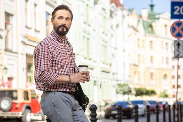 Житель города. серьезный красавец пьет кофе, стоя на улице