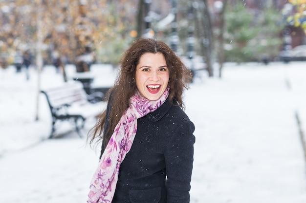 都市、感情、人々の概念-黒いコートとピンクのスカーフの美しく幸せな女性が持っています