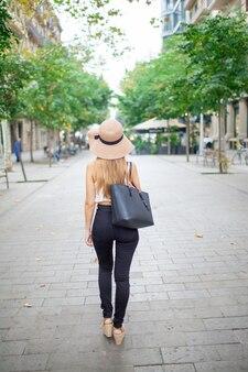 歩行者の通りを歩いている市の少女