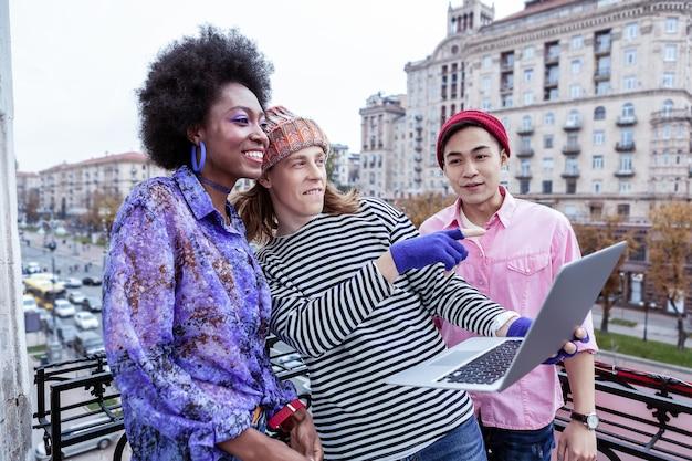 シティガイド。歩く前にシティガイドビデオを見ている3人のアクティブな若いスタイリッシュな旅行者