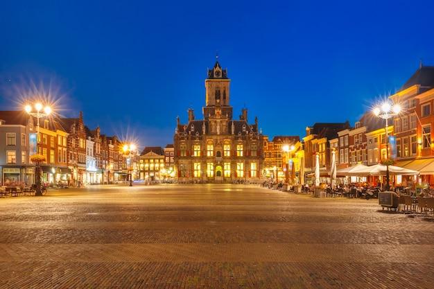 시청과 밤, 델프트, 네덜란드, 네덜란드의 오래된 도시 중심에있는 markt 광장에있는 전형적인 네덜란드 주택