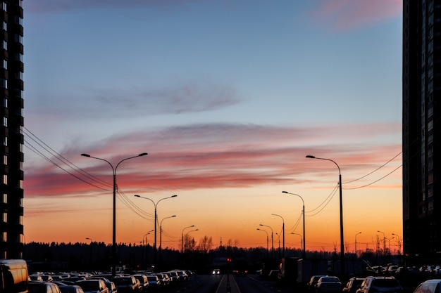 City highway at sunset. road with lots of parked cars, some buildings, and road lights