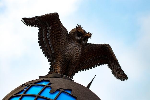 街のランドマーク、青い空を背景に世界の地球儀を持つ金属のフクロウ。