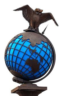 街のランドマーク、白い背景で隔離の世界の地球儀と金属フクロウ。
