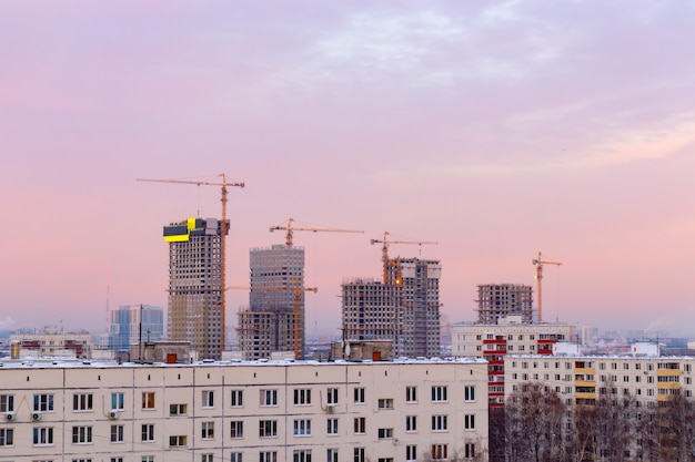City landscape at dawn, sunrise with beautiful skyline and buildings under constructions with cranes