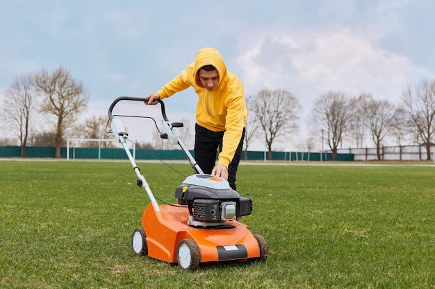 芝刈り機が植えられた周りの草を刈る都市造園家の男庭師労働者