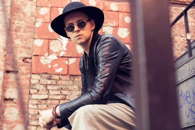都市生活。トレンディな服装の若いスタイリッシュな男が階段に座っています