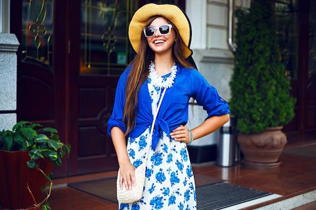 通りで楽しんで一人で歩いている幸せなかわいい女の子、夕方の日光、レトロなドレスのヴィンテージ帽子、幸せなポジティブな気分の都市ライフスタイルファッションの肖像画。