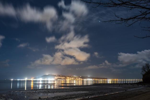 街の明かりとドーセット、イギリスのサンズフットビーチからの夜空
