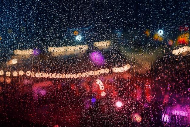 Огни ночного города во время дождя за стеклом, покрытым каплями воды.