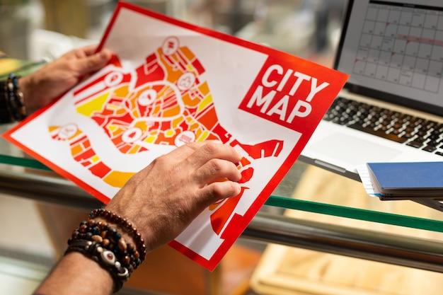 Карта города. руки туриста, носящего браслеты шамбалы, держат карту города в поисках лучшего способа прогуляться.