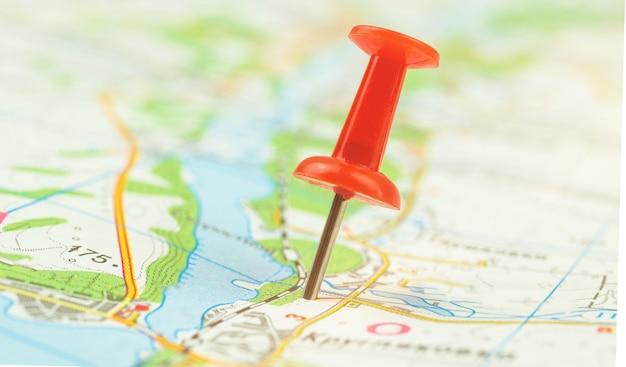 Концепция городской навигации, красная канцелярская кнопка на карте, фото фона картографии