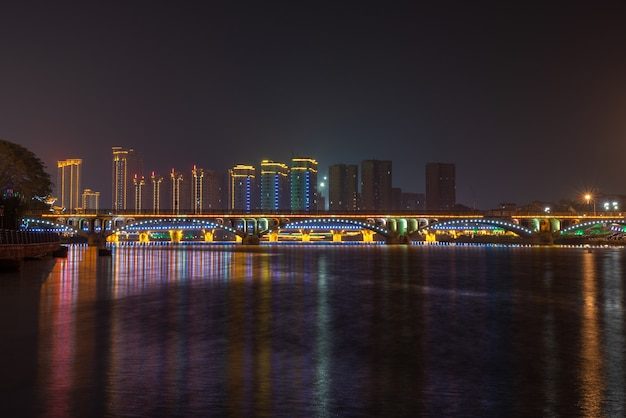 In the city at night, colorful lights are reflected in the water of the river