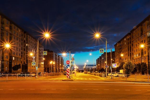 Городская ночная улица с многоэтажными домами, пешеходным переходом, дорогой и яркими фонарями