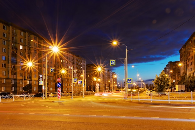 Городская ночная улица с многоэтажными домами, дорогой и яркими фонарями.