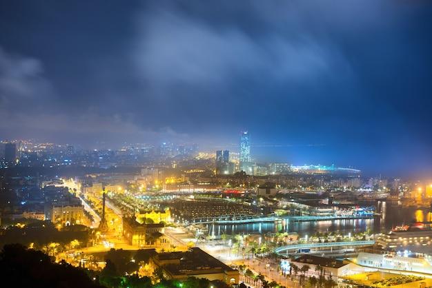 夜のバルセロナ市。青い暗い空と港と街並みの眺め