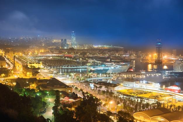 밤에 바르셀로나의 도시입니다. 푸른 어두운 하늘이 있는 항구와 도시 경관