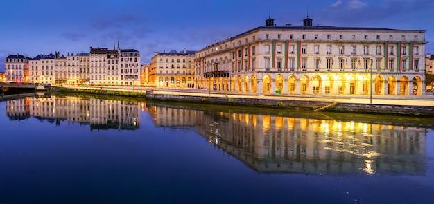 夜のフランスのバイヨンヌ市。典型的な建築物の家々とアドゥー川の反射。ヨーロッパ。