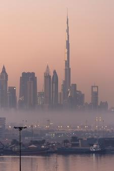 霧の夕日とドバイの街