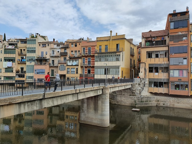 Город на реке, мост и улица старого города с цветными домами летом